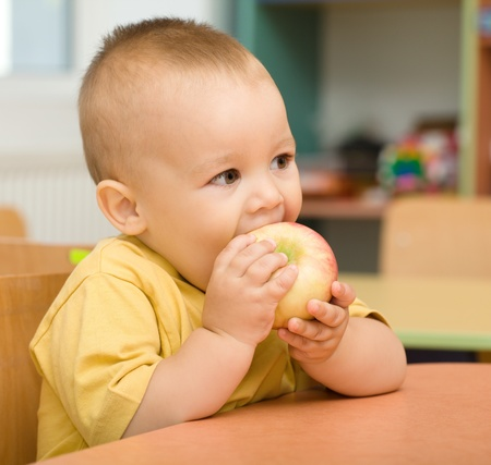 Cute boy is eating apple in preschool photo