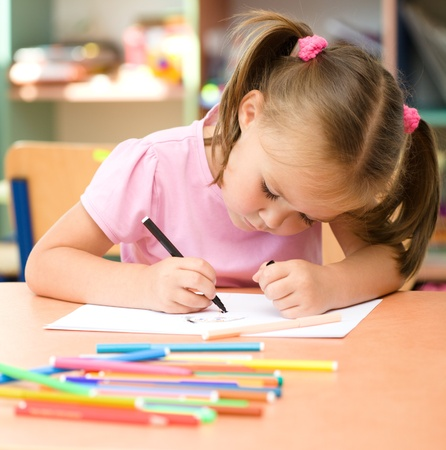 daycare: Cute little girl is drawing with felt-tip pen in preschool Stock Photo