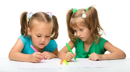 Two little girls draw with markers while sitting at table, isolated over white photo