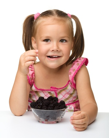 Cute cheerful little girl is eating blackberry, isolated over white