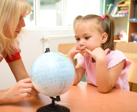 Little girl on geography lesson listening to the teacher and looking at globe photo