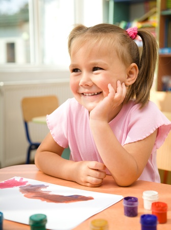Cute little girl is play with paints in preschool