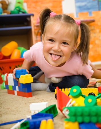 Little girl is showing tongue while playing with building bricks in preschool photo