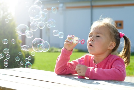 focused: Cute little girl is blowing soap bubbles while sitting at table outdoors