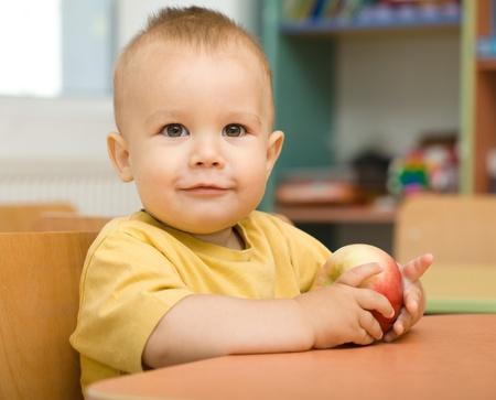 daycare: Cute boy is eating apple in preschool