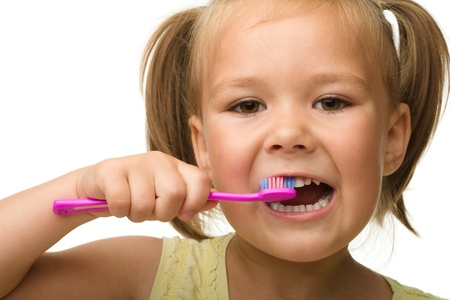 Cute little girl is cleaning teeth using toothbrush, isolated over white photo
