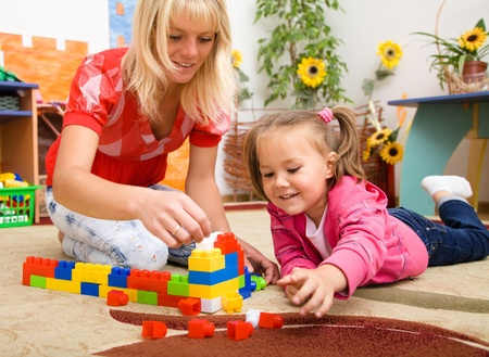 childcare: Teacher and child are playing with building bricks in preschool Stock Photo