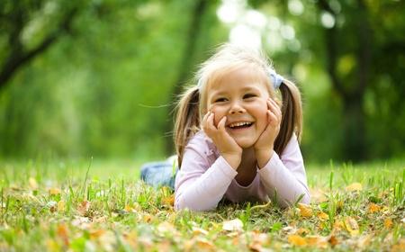 jugar: La niña linda está jugando con las hojas en el otoño de parque