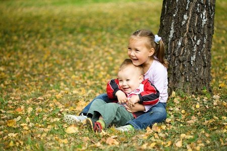 Cute children are playing in autumn park photo