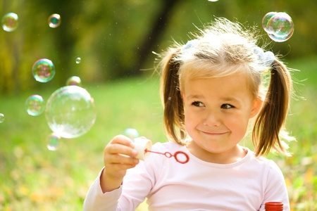 burbujas de jabon: Niña linda está soplando pompas de jabón