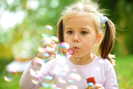 children playing outside: Cute little girl is blowing a soap bubbles