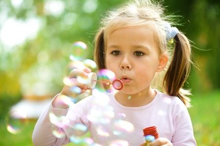 burbujas de jabon: Linda ni�a sopla un pompas de jab�n