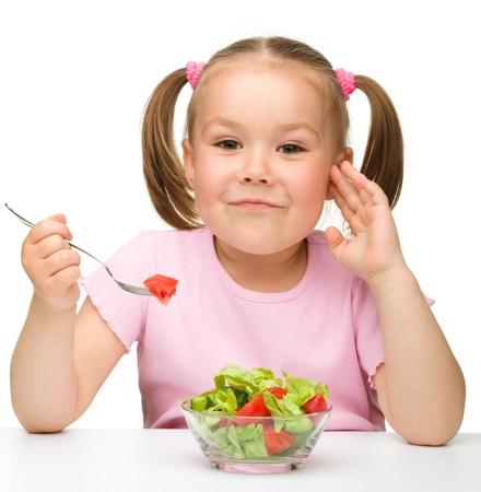 Cute little girl eats vegetable salad using fork, isolated over white photo