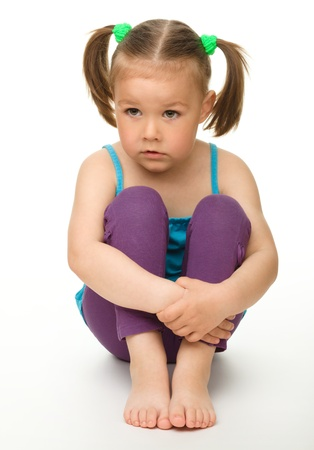 sitting on: Portrait of a cute little girl sitting on floor, isolated over white
