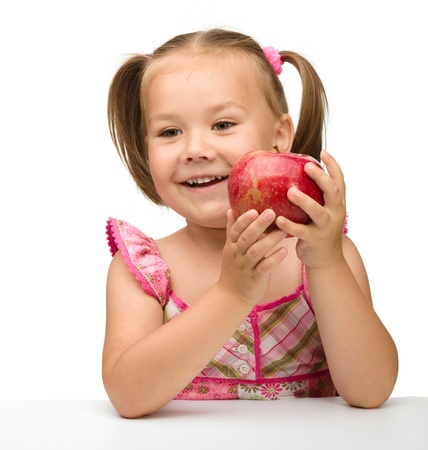 Portrait of a cute cheerful little girl with red apple, isolated over white Imagens