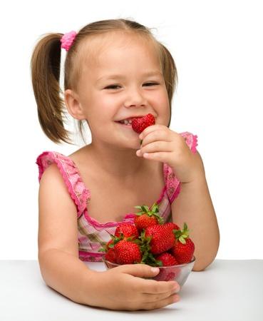 Felice bambina mangia fragole, isolato su bianco