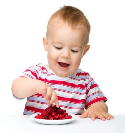 Netter kleiner Junge mit Erdbeeren, isoliert über weiß