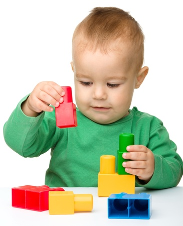 playschool: Cute little boy is playing with building bricks while sitting at the table, isolated over white