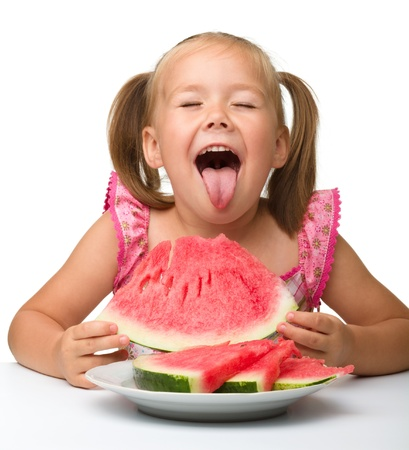 Cute little girl is gungy to eat watermelon, isolated over white photo