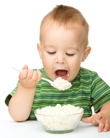 over eating: Cute little boy is eating cottage cheese using spoon, isolated over white Stock Photo