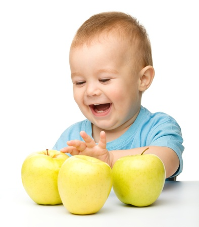 Portrait of a cute little child with three yellow apples, isolated over white photo