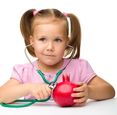 Portrait of a cute little girl with pomegranate and stethoscope, isolated over white photo