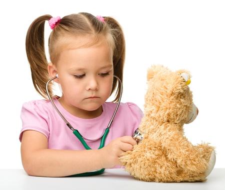 pediatrics: Little girl is examining her teddy bear using stethoscope, isolated over white Stock Photo