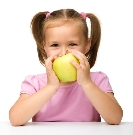 Portrait of a cute little girl with yellow apple, isolated over white photo