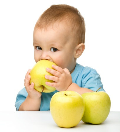 Portrait of a cute little child biting yellow apple, isolated over white photo
