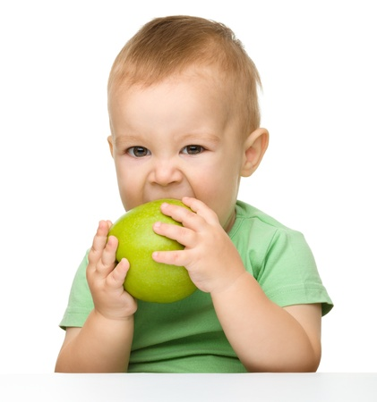 bite: Cute little child is eating green apple while sitting at table, isolated over white