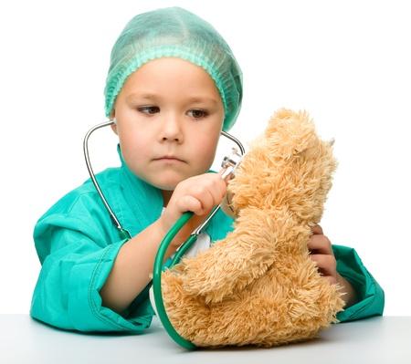 bebe enfermo: Ni�a linda est� jugando al doctor con un estetoscopio y un oso de peluche, aislado m�s de blanco