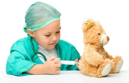 persona sentada: Ni�a linda que es jugar al doctor con una jeringa y osito de peluche, aisladas en blanco