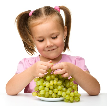 over eating: Little girl is eating grapes, isolated over white