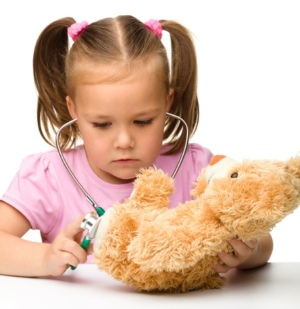 Little girl is examining her teddy bear using stethoscope, isolated over white photo