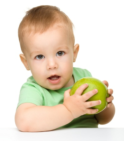 Cute little child is eating green apple while sitting at table, isolated over white photo