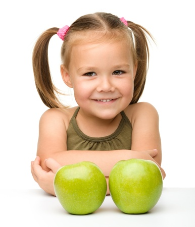 close up food: Portrait of a cute little girl with two green apples, isolated over white