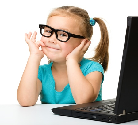 little table: Cute little girl is sitting at table with her black laptop and wearing glasses, isolated over white Stock Photo