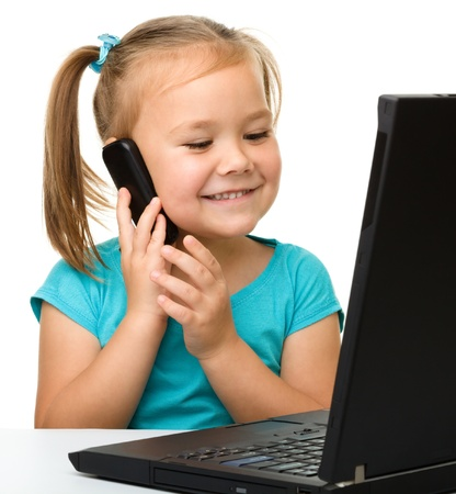Cute little girl is sitting at table with her black laptop and talking to a cell phone, isolated over white Stock Photo - 11554889