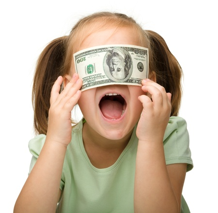 Cute little girl is covering her eyes with dollars, isolated over white photo