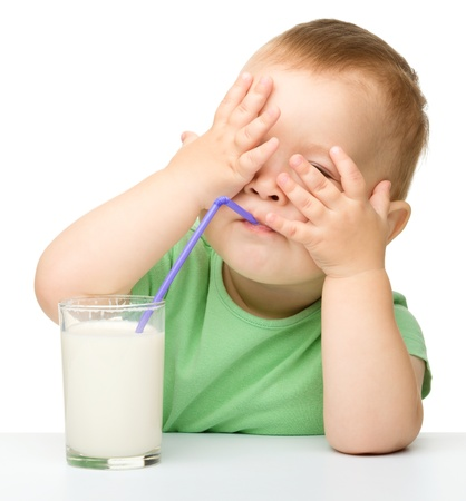 Cute little boy is drinking milk while hiding his eyes using hands, isolated over white