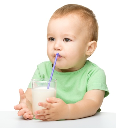 Cute little boy is drinking milk using straw while sitting at table, isolated over white photo