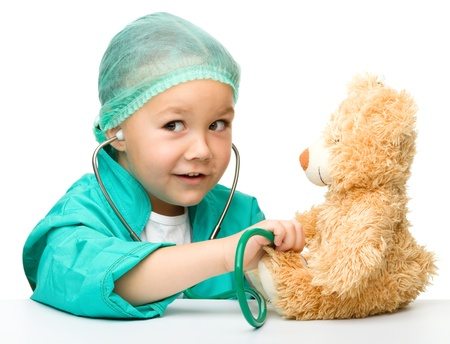 Cute little girl is playing doctor with stethoscope and teddy bear, isolated over white photo