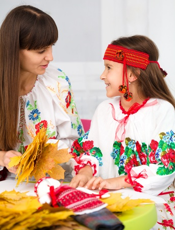 Mother and child in Ukrainian national cloth doing crafts photo
