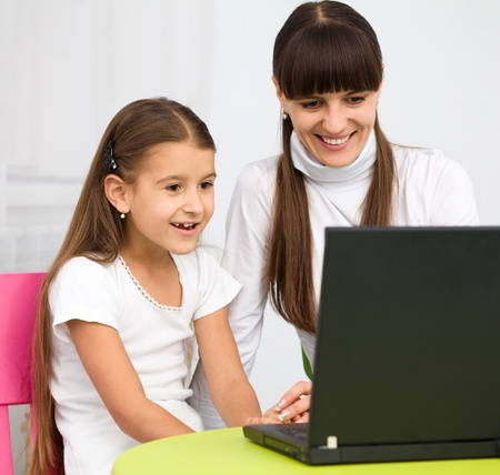 Mother an her daughter are playing with laptop Stock Photo - 11555010