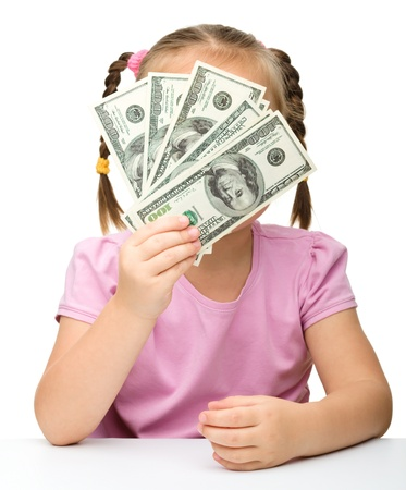 Cute little girl is covering her face with dollars, isolated over white photo