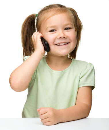 Cute little girl is talking on cell phone while sitting at table, isolated over white Imagens