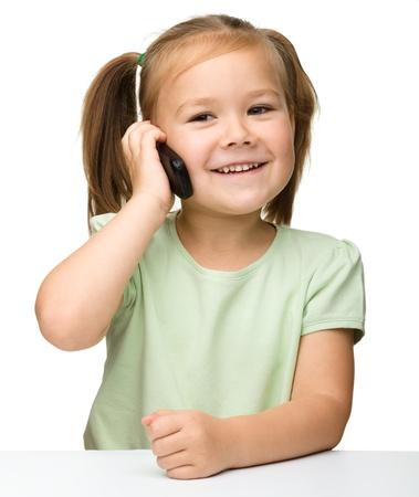ni�os hablando: Ni�a linda est� hablando por tel�fono celular mientras se est� sentado a la mesa, aislado m�s de blanco Foto de archivo