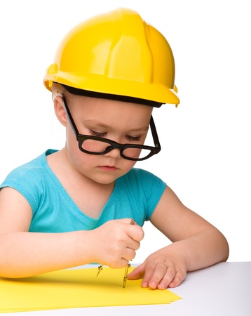 Cute little girl play with divider wearing hard hat, isolated over white