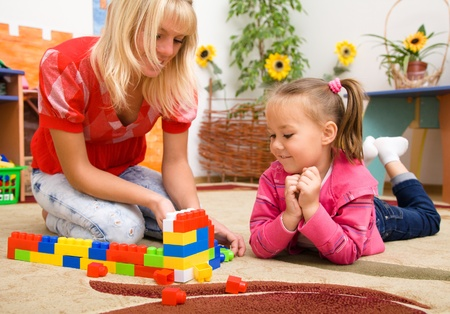 CHILD CARE: Teacher and child are playing with building bricks in preschool Stock Photo