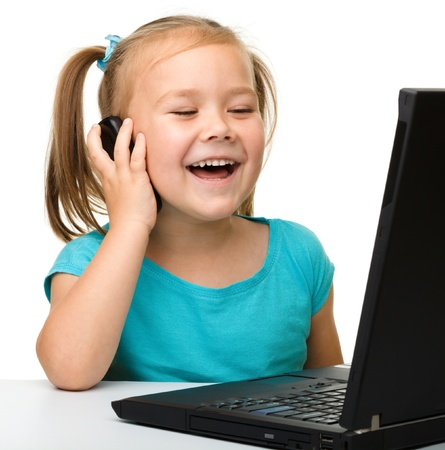 Cute little girl is sitting at table with her black laptop and talking to a cell phone, isolated over white photo